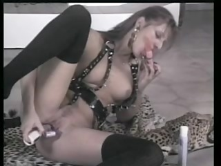 sexy blonde in leather uses a big fake pecker on